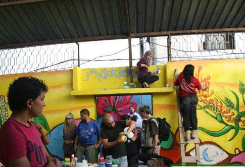 مجموعة من الفنانين والفنانات العالمين برسوم جدارية في مكان النصب الذكاري في مخيم البرج الشمالي