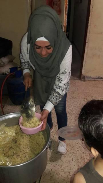 لجان المرأة الشعبية في مخيم البرج توزع وجبة إفطار على النازحين من سوريا